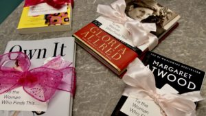 Womens History Month photo of books with pink ribbons